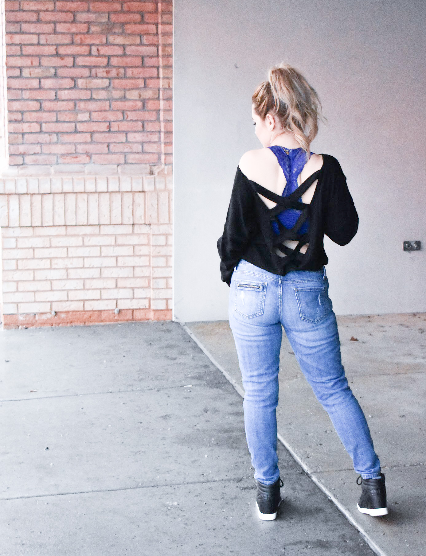 Black Criss-Cross Sweater + Bralette for Large Bust: This black criss-cross sweater styled with ripped jeans and black wedge sneakers is the perfect mix of sporty and sexy for your next date night! Plus, the perfect affordable bralette for large bust ladies. Fashion blogger COVET by tricia shows how to style a perfect date night look mixing black and denim.