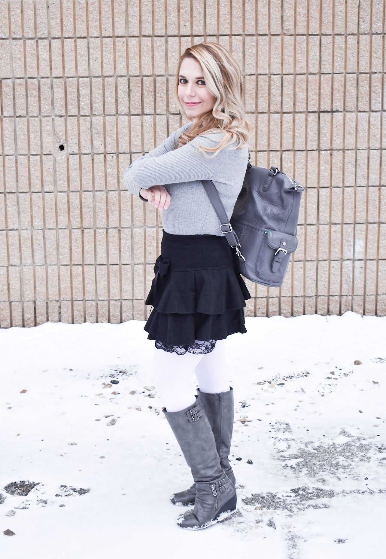 Fashion blogger COVET by tricia styles a ruffled black mini skirt with white tights, a grey bodysuit, grey wedge boots ,and a gorgeous Lily Jade diaper bag. This black mini skirt with ruffles is an affordable statement piece for your wardrobe. Check out this cute winter date night look from Kansas City fashion blogger COVET by tricia.